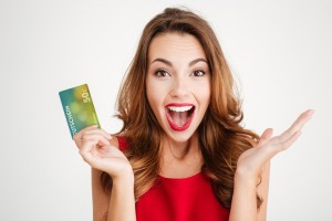 Happy excited amazed young woman holding credit card over white background